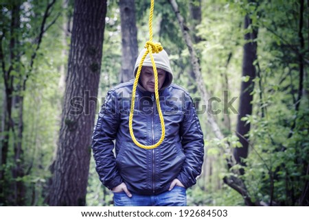 The noose before the man in the dark woods - stock photo