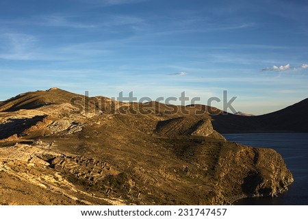 The Northern part of Isla del Sol (Island of the Sun), a popular tourist destination on Lake Titicaca, Bolivia before sunset. In the left lower corner the Tiwanaku-Inca ruin Chinkana is visible. - stock photo