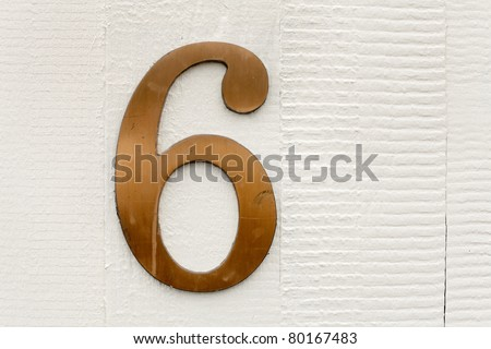 The number six in brass attached to a house wall - stock photo