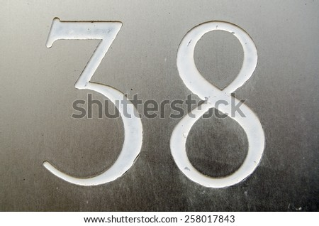 The number thirty eight incised and painted into a stainless steel plate outside a house.  Viewed from public pavement. - stock photo