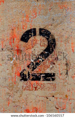 The number 2 (two) painted in black on a multi-colored background at an industrial facility. - stock photo
