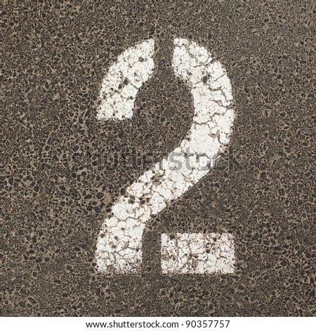The number Two stencil painted in white on the ground of a  carpark - stock photo