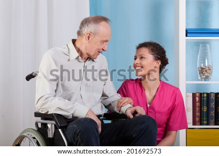 The nurse smiles to sitting in a wheelchair patient - stock photo