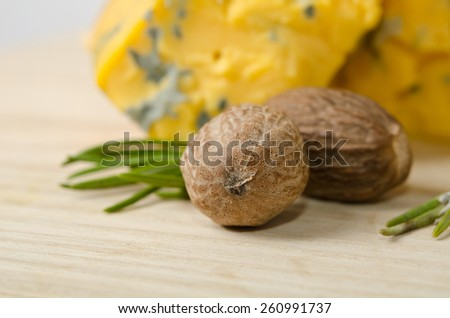 the nutmeg with two pieces of cheese on wooden table - stock photo