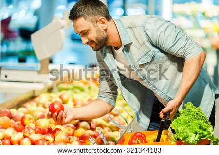 The nutritional choice. Handsome young man holding apple and shopping bag while standing in a food store  - stock photo