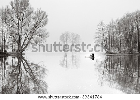 The oarsman in a boat floats on lake in November. - stock photo