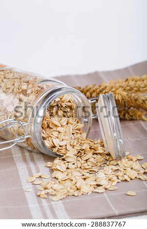The oat flakes spilling out of glass jar.  - stock photo