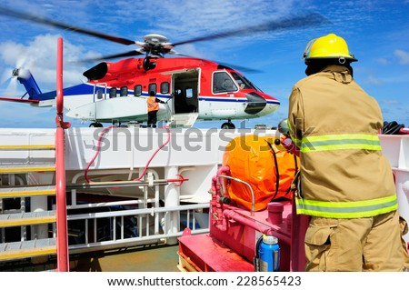 The offshore fireguard standing by on the helideck with the helicopter waiting for passengers - stock photo