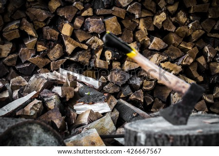 the old axe stuck in a stump, on a background of chopped firewood - stock photo