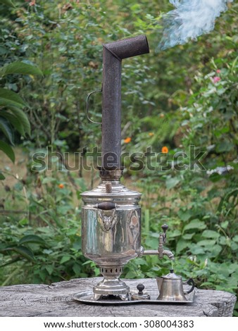 The old beginning to boil samovar on a stub. - stock photo
