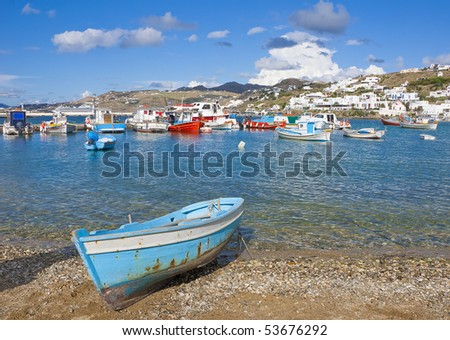 The old blue boat on the beach in the town of Mykonos on the background of the sky with clouds and fishing boats - stock photo