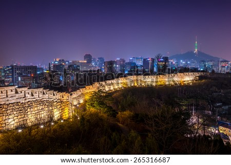 The old city wall lit up in evening as the lights of downtown Seoul shine in the distance. - stock photo