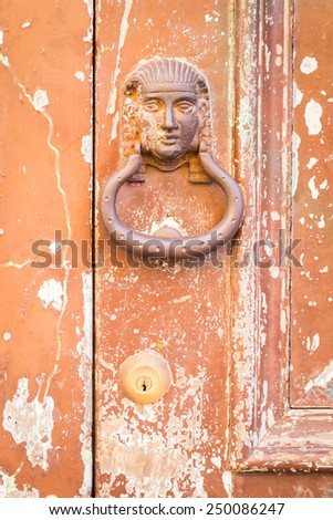 The old door handle in the form of the pharaoh on the old cracked door. Texture of old painted wood. - stock photo