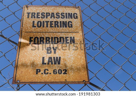 """The old """"Forbidden by law"""" sign on the chain link fence. - stock photo"""