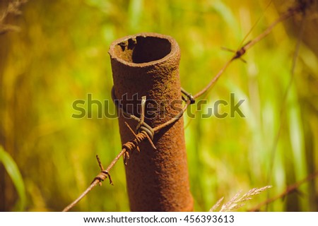 the old guard. rusty barbed wire and pipe - stock photo