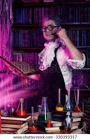 The old man medieval scientist working in his laboratory. Alchemist. Halloween. - stock photo