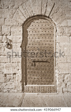 The old medieval door. Old style. Sepia - stock photo