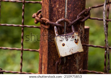 The old Old rusty gate lock on a old iron door. - stock photo