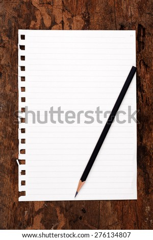 The old page ripped off from the notebook on wood texture - stock photo