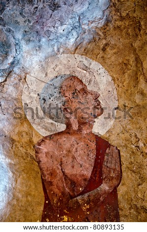 The Old painting of buddha status in cave. This is traditional and generic style in Thailand. No any trademark or restrict matter in this photo. - stock photo
