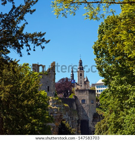 The old part of Luxembourg on a beautiful day in Spring. Parts of the Case-mates and a church nicely framed by green trees growing in the city - stock photo