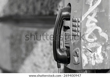 the old payphone with receiver is fixed on a stone wall in monochrome tones with a blank space for the text - stock photo
