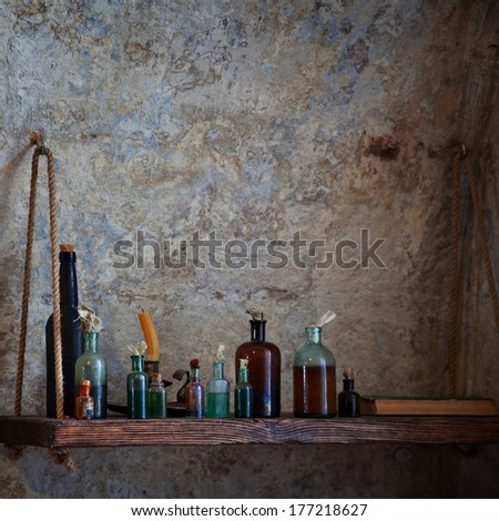 The old pharmacist's bottle with liquids on the shelf against the dilapidated walls  - stock photo