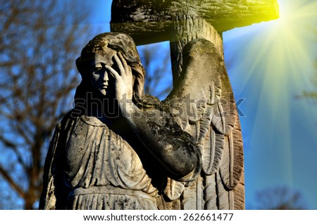 The old stone statue of an angel in light sunlight (doomsday, apocalypse, the coming of Christ, good and evil - the concept) - stock photo