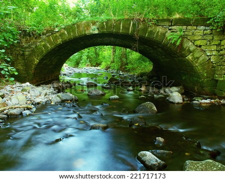 The old stony bridge of mountain stream in leaves forest, blue blurred water is running over boulders.  - stock photo