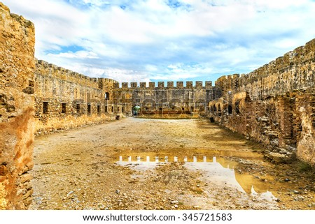 The old Venetian fortress Frangokastello.Inner courtyard.in the puddles on the ground reflected the loopholes and fortress walls.Crete island.District of Chania. Greece.Europe. - stock photo