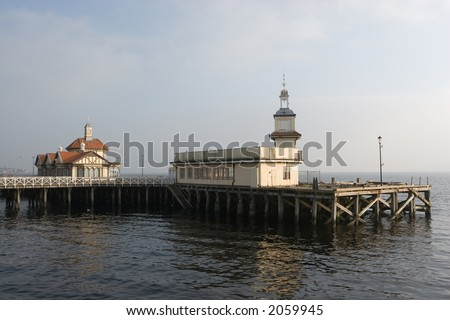 The old Victorian pier and ferry terminal at Dunoon, Scotland, with the mist in the background. - stock photo