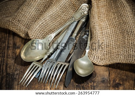 The old wooden table cutlery on the burlap. - stock photo