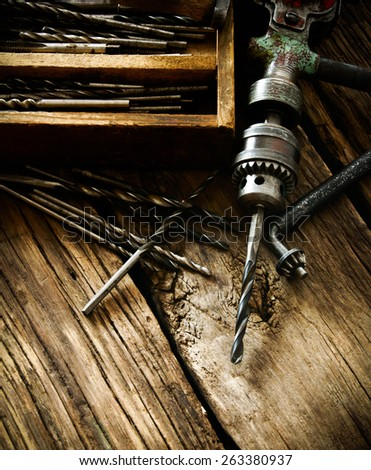 The old working tool. An old drill, a box with drills on a wooden background. - stock photo
