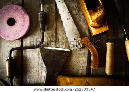 The old working tool. Many old working tools ( axe, saw and others) on a wooden background. - stock photo
