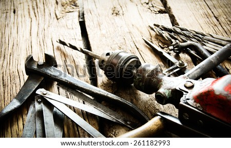 The old working tool. Old drill, compasses, pliers and drills on a wooden background. - stock photo