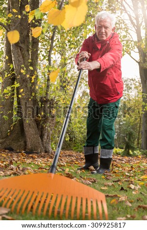 The older man while working in the garden - stock photo