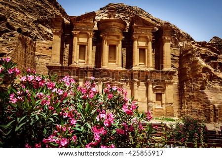 The oleander shrubs and Monastery Ad-Deir, ancient Nabataean city Petra, Jordan. - stock photo