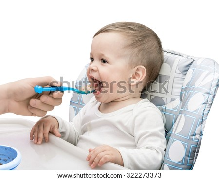 The one-year-old kid eats porridge isolated on the white - stock photo