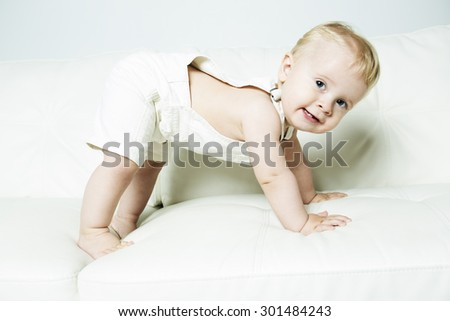 The one-year-old kid learns on a sofa - stock photo