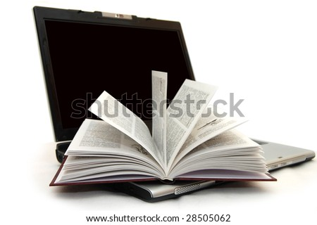 The open book laying on the laptop - stock photo