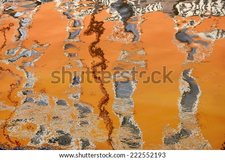 The orange reflection of buildings in water - stock photo