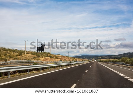 The Osborne bull is a 14-metre (46 ft) high black silhouetted image of a bull and is regarded as the unofficial national symbol of Spain. There are approximatley 91 on alongside the Spanish roads. - stock photo