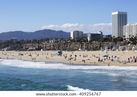 The Pacific ocean and a clear day, Santa Monica. Beach landscape in the USA with blue sea and mountain ranges. People relax on the beach.  - stock photo