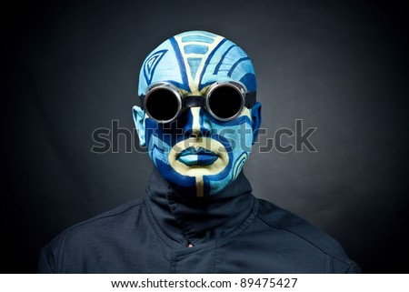The painted man's face on a black background. Dark goggles - stock photo