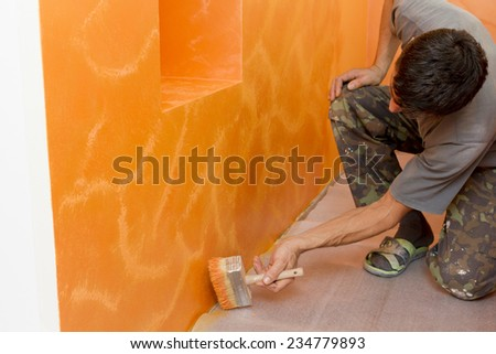 The painter paints the wall decorative paint. - stock photo