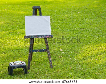 The painting board on fresh green grass - stock photo