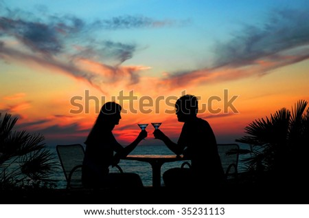 The pair silhouette is held by goblet on a sundown - stock photo