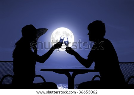 The pair silhouette is held by goblet with wine on a moon night - stock photo