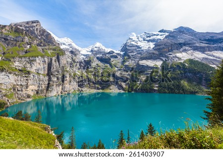 The panorama in summer view over the Oeschinensee (Oeschinen lake) and the alps on the other side near Kandersteg on bernese oberland in Switzerland. - stock photo
