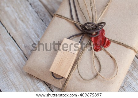 The parcel wrapped in Kraft on a wooden background. The gift wrapped in Kraft. Wooden USB stick. Cord and red sealing wax. - stock photo